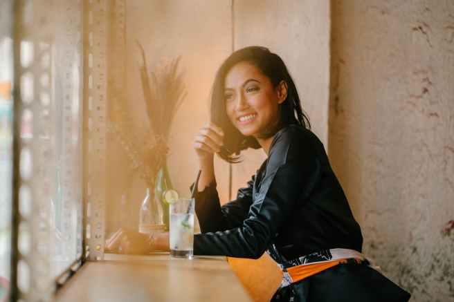 woman sitting on bar chair near clear drinking glass