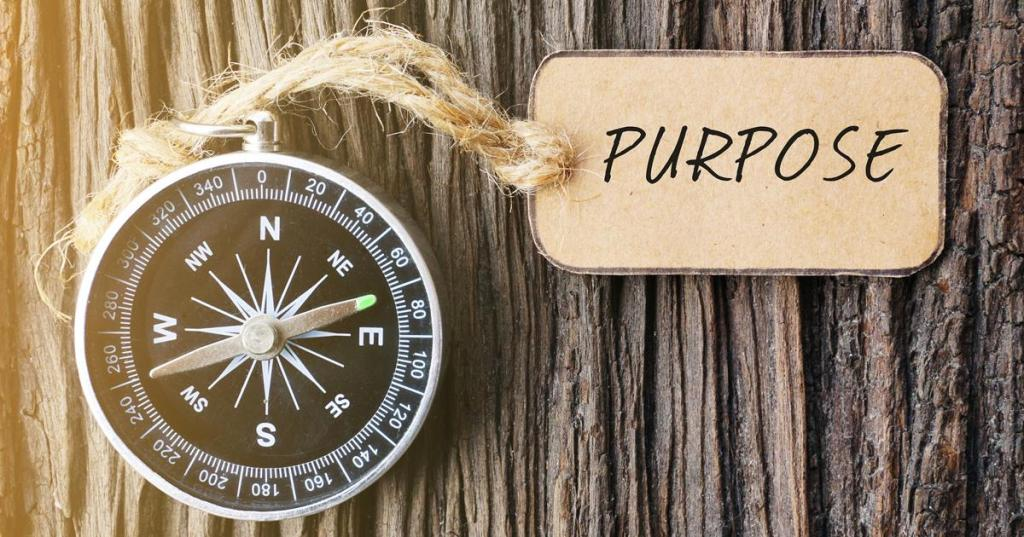 Magnetic compass and paper tag written with PURPOSE text on old wooden background. A concept. www.clemmergroup.com